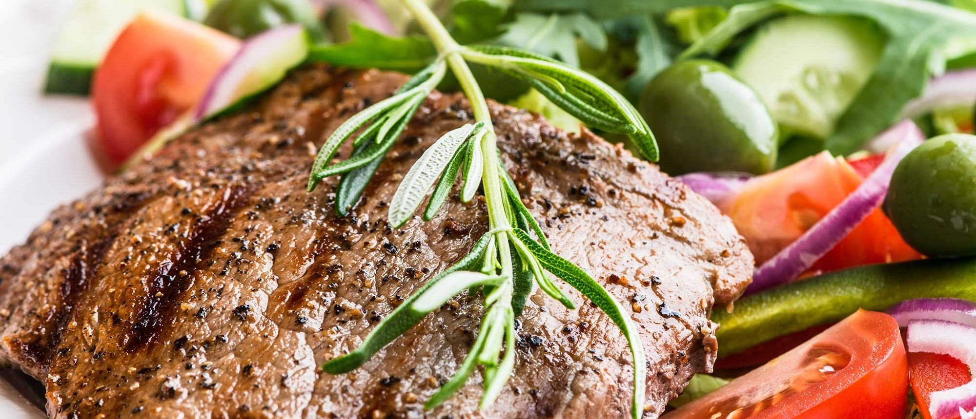 Grilled beef steak with salad and rosemary sprig.