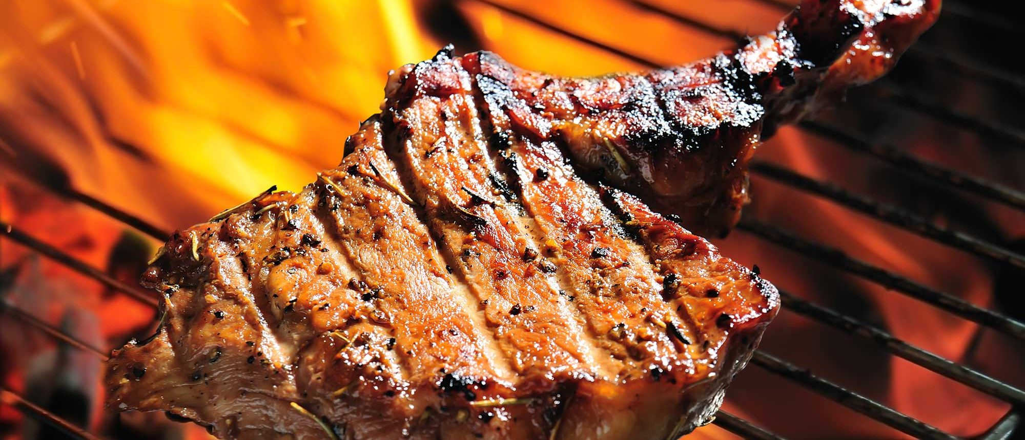 Steak being grilled over an open flame.