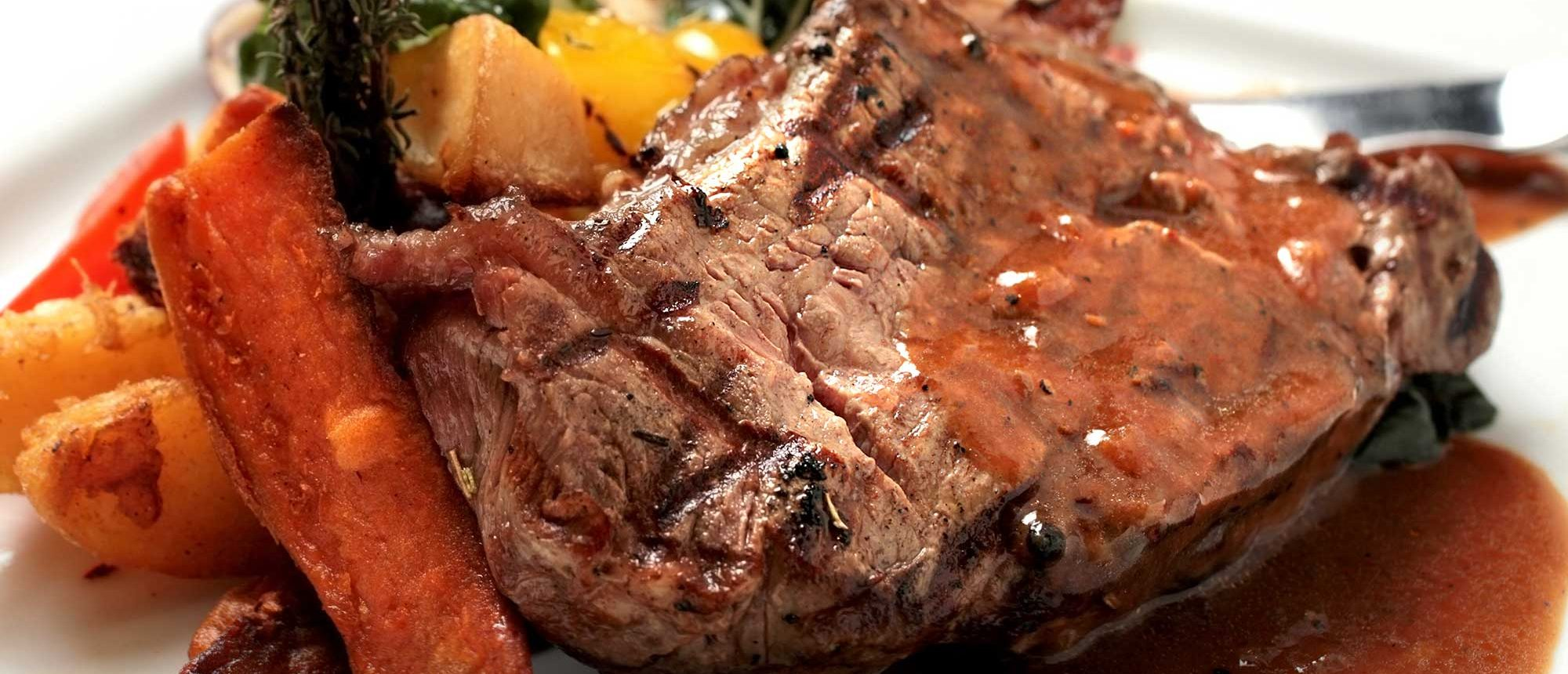 Beef steak served with barbecue sauce.