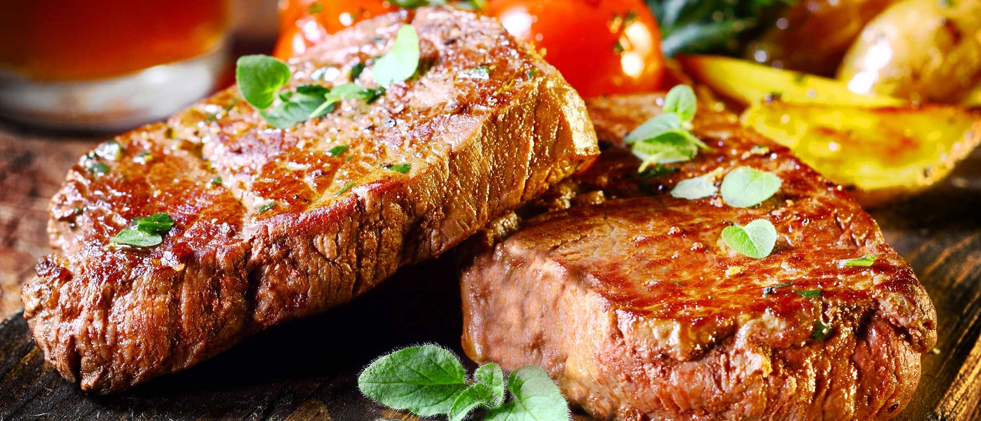 Succulent thick juicy portions of grilled fillet steak served with tomatoes and roast vegetables on an old wooden board.